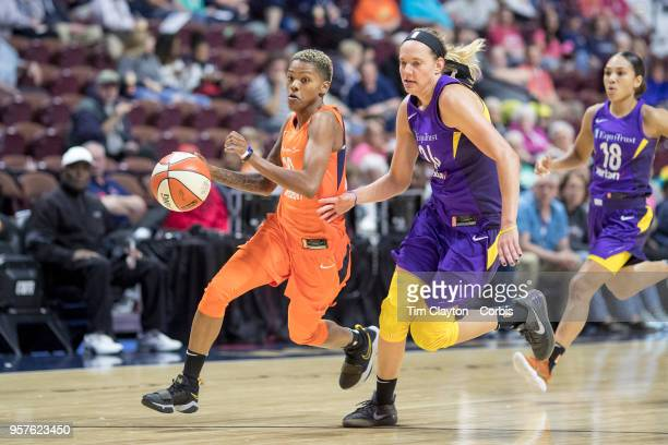 Courtney Williams of the Connecticut Sun drives to the basket defended by Sydney Wiese of the Los Angeles Sparks during the Connecticut Sun Vs Los...