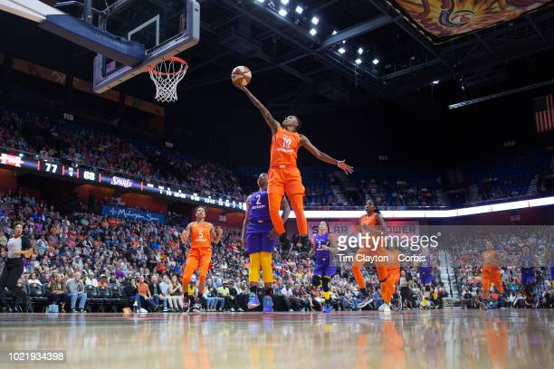 Courtney Williams of the Connecticut Sun scores two points on a break away watched by Riquna Williams of the Los Angeles Sparks during the...