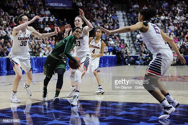Courtney Williams USF drives to the basket defended by Breanna Stewart Katie Lou Samuelson and Gabby Williams UConn during the UConn Huskies Vs USF...