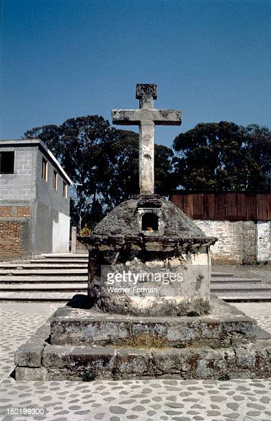 Courtyard cross at the church of La Virgen de la Candelaria, Cuidad Hidalgo, Candles are lit in a small altar at the base. Disks of obsidian, which...