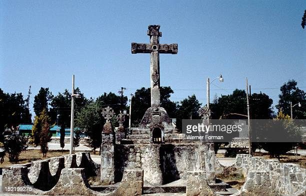 Courtyard with church cross at San Felipe de los Alzati south of Cuidad Hidalgo Christian symbols such as the Franciscan shield showing the Five...