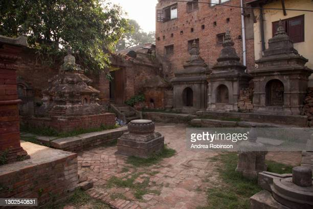 a courtyard with small stone temple structures and stupa's alongside shiva lingam's adjacent to the giant shiva lingam in the hanuman ghat area of bhaktapur in the kathmandu valley, nepal. - shiva lingam stock pictures, royalty-free photos & images