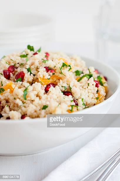 cous cous salad with pomegranate seeds, clementine, chopped mint and flat leaf parsley - flat leaf parsley stock photos and pictures