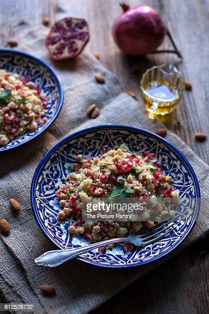 Couscous with chickpeas, almonds and pomegranate on ceramic blue plates and rustic wooden table