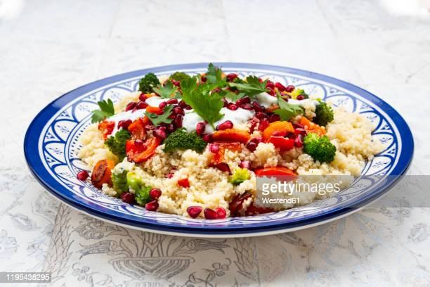 couscous with grilled vegetables: carrots, peppers and broccoli and yoghurt-mint sauce, parsley, pomegranate seeds - couscous stock pictures, royalty-free photos & images