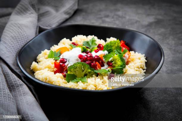 couscous with grilled vegetables, yoghurt-mint sauce, parsley, and pomegranate seeds - larissa veronesi stock-fotos und bilder