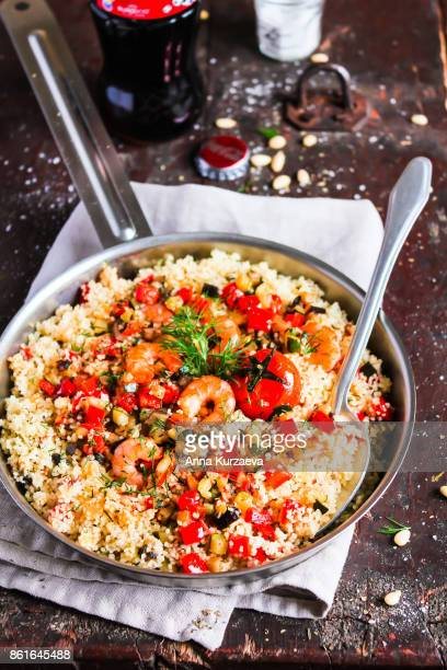 couscous with roasted bell pepper, eggplant, zucchini, cherry tomatoes, shrimps in a pan, selective focus - couscous marocain photos et images de collection
