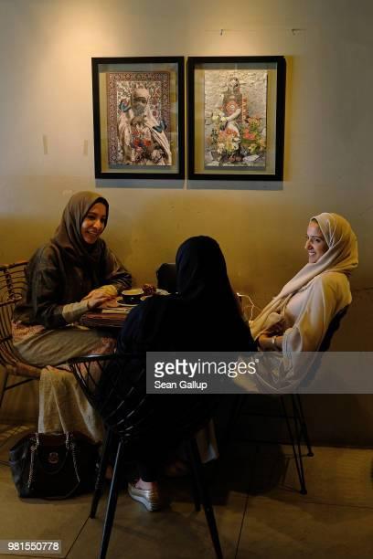 Cousins Heba Hariri Duaa Hamadah and Asmaa Hamadah chat at Medd Cafe and Roastery a popular hangout for creative Saudis on June 21 2018 in Jeddah...