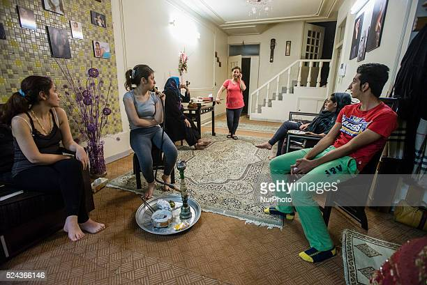Cousins of Parsa science student smoke qelyan after dinner traditional kind of entertainment in Iranian families while his aunt Fara speaking with...