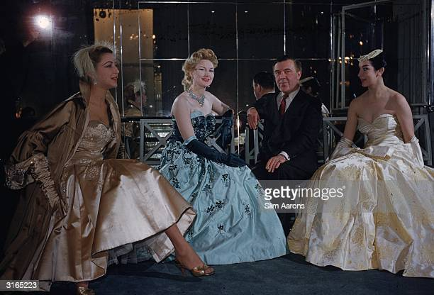 Couturier and court dressmaker Norman Hartnell with three models at his Burton Street salon, London.