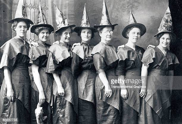Coven of witches' line up for a Halloween portrait dressed in festive witch's hats and improvised costumes, ca.1910, United States.