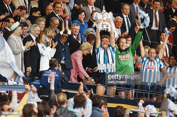 Coventry City captain Brian Kilcline lifts the trophy after the 1987 FA Cup Final between Coventry City and Tottenham Hotspur at Wembley Stadium on...