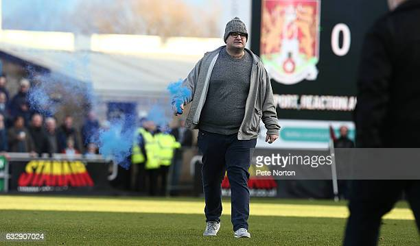 Coventry City fan holding a flare during a pitch invation during the Sky Bet League One match between Northampton Town and Coventry City at Sixfields...