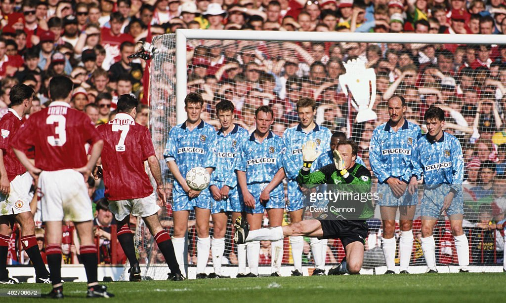 Coventry City goalkeeper Steve Ogrizovic and the City defensive wall attempt to stop a free kick from Eric Cantona as a fan from behind the goal waves a foil Premier League trophy during the final game of the 1993/94 season, as champions Manchester United draw 0-0 with Coventry City at Old Trafford on May 8, 1994 in Manchester, England.
