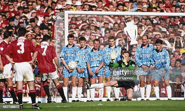 Coventry City goalkeeper Steve Ogrizovic and the City defensive wall attempt to stop a free kick from Eric Cantona as a fan from behind the goal...