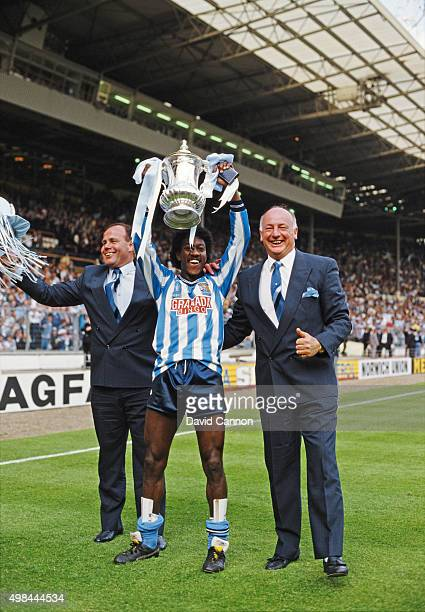 Coventry City goalscorer Dave Bennett lifts the trophy flanked by managerial team George Curtis and John Sillett after the 1987 FA Cup Final between...