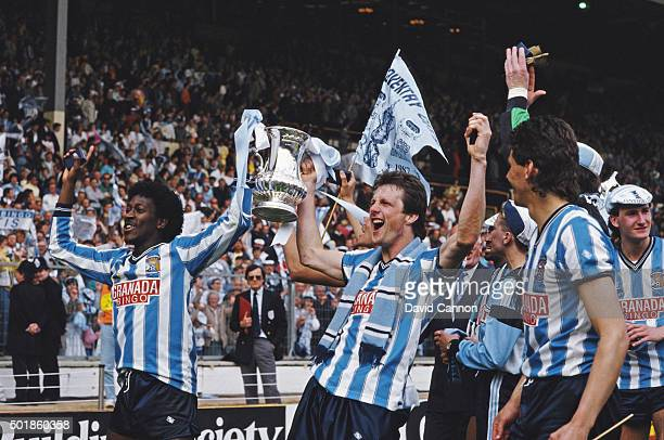 Coventry goalscorers Dave Bennett and Keith Houchen hold the trophy aloft after the 1987 FA Cup Final between Coventry City and Tottenham Hotspur at...