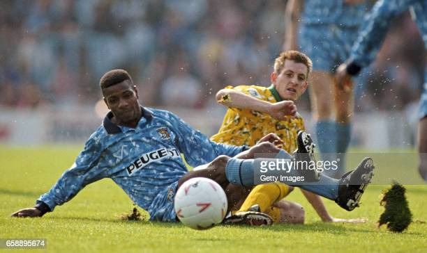 Coventry player Lloyd McGrath is challenged by Ian Crook of Norwich as a divot of turf is churned up during the FA Premier League match at Highfield...