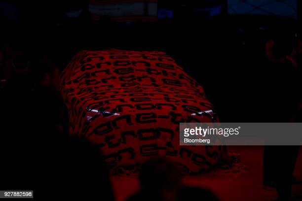 A cover sits on the new Audi etron prototype automobile at the Audi AG stand on the opening day of the 88th Geneva International Motor Show in Geneva...