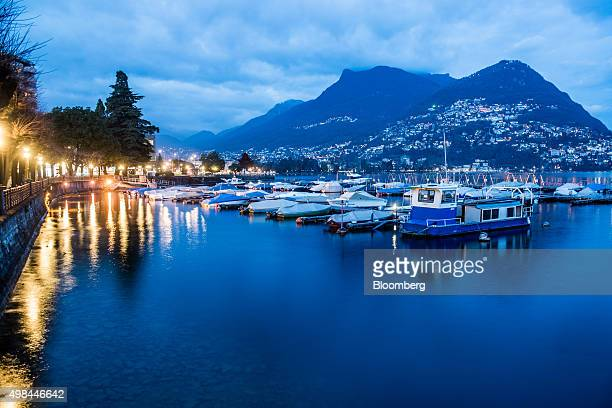 Covered boats sit moored to a jetty on Lake Lugano at dusk in Lugano Switzerland on Friday Nov 20 2015 The franc is still too strong and the economy...