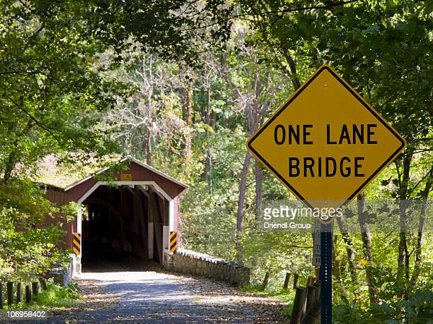 a covered bridge and road sign. - covered bridge stock pictures, royalty-free photos & images