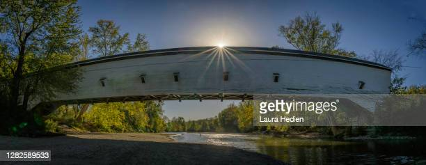 covered bridge in the autumn with sun flare - indiana stock pictures, royalty-free photos & images