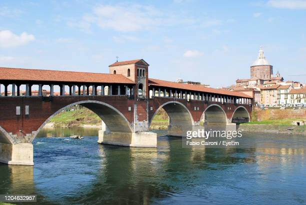 covered bridge over the ticino river from borgo ticino in pavia, lombardy, italy. - covered bridge stock pictures, royalty-free photos & images
