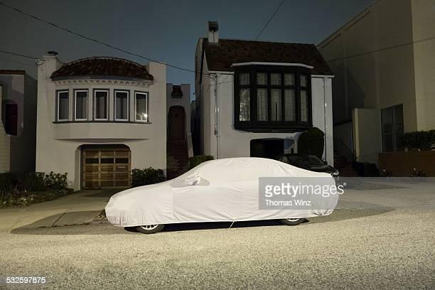 Covered car at night