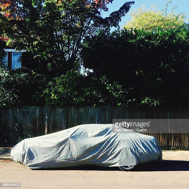 Covered Car Parked On Street During Sunny Day