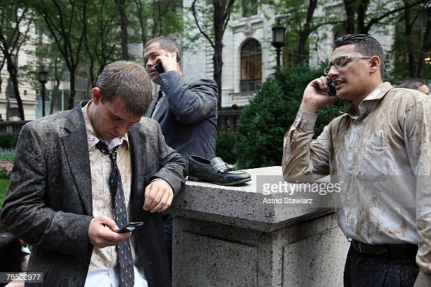 Covered in debris Eric Duberice Will Ozier and Santos Rivera talk on their cell phones in front of the New York Public Library after walking away...