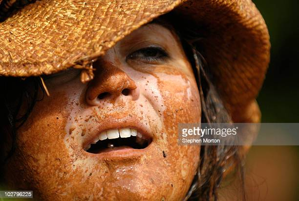 Covered in mud, Christy Hutchins talks with friends after diving into a mud pit used for the annual Mud Pit Belly Flop contest during the 14th Annual...