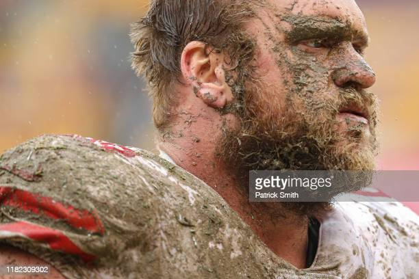 Covered in mud offensive guard Mike Person of the San Francisco 49ers looks on after making a tackle on defensive back Troy Apke of the Washington...