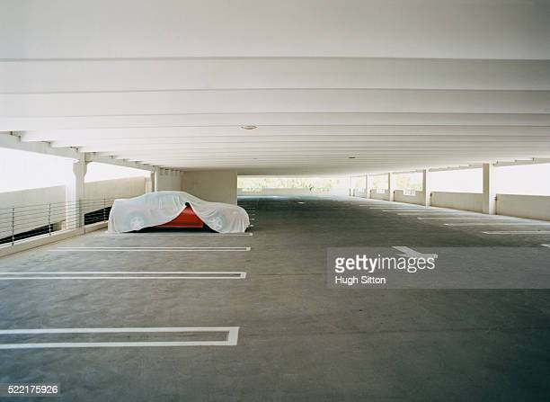 covered red car in empty parking lot - hugh sitton stock pictures, royalty-free photos & images