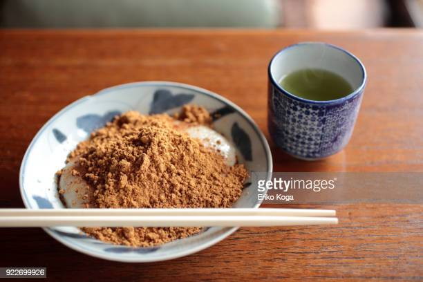 covered rice cake with roasted soybean flour called kinako-mochi and japanese tea - kinako stock pictures, royalty-free photos & images