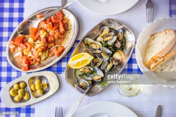covered table with delicious clams served on silverware, white wine, tomato salad, bread and olives from above, portugal - cultura portuguesa fotografías e imágenes de stock