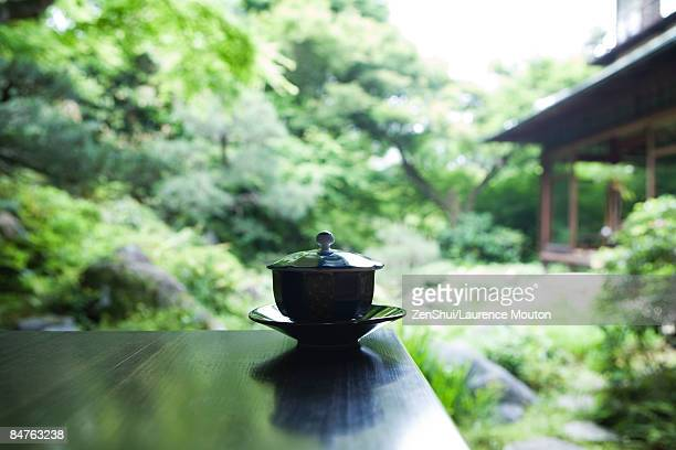 Covered tea cup and saucer on table, Japanese garden in background