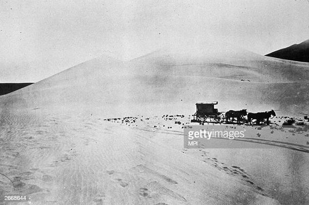 A covered wagon makes its way across the Carson Desert Nevada This is the mobile darkroom of Timothy O'Sullivan as official photographer during the...