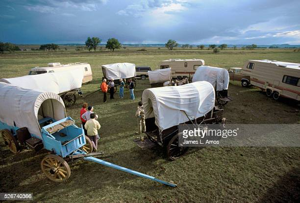 Covered wagons and motor homes stand in a circle in imitation of the protective circles pioneers formed as they set up camp while crossing the...