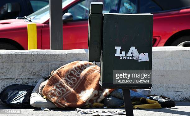 Covered with a blanket a homeless man sleeps along a Hollywood sidewalk on March 7 2012 in California A new study by the National Poverty Center on...