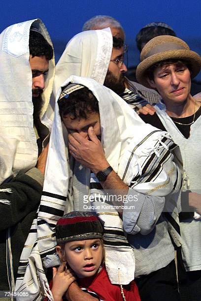 Covered with a prayer shawl, Haim Hoter cries as he comforts his son Avihai during the funeral of his other son Gabriel Hoter December 29, 2002 in...