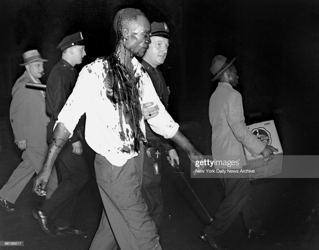 Covered with blood a man is being taken to the West 123d St. precinct station on August 2, 1943 in Harlem, New York. He was arrested in bar and grill at 124th St. and Seventh Avenue. Station houses were crowded with arrested looters.