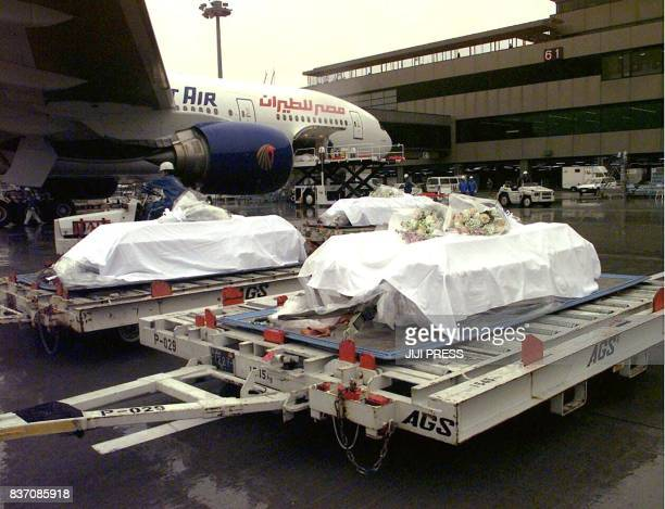Covered with white palls 10 coffins of the Japanese victims from the Luxor massacre are unloaded from the airplane after returning from Egypt with...