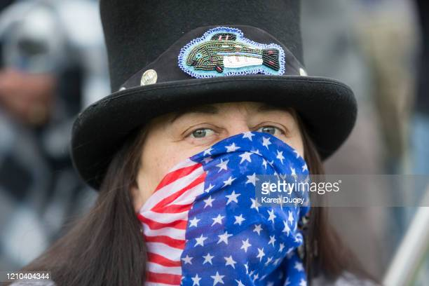 Covering her face with a red white and blue scarf Susan Keen attends a 'Hazardous Liberty Defend the Constitution' rally to protest the stayathome...