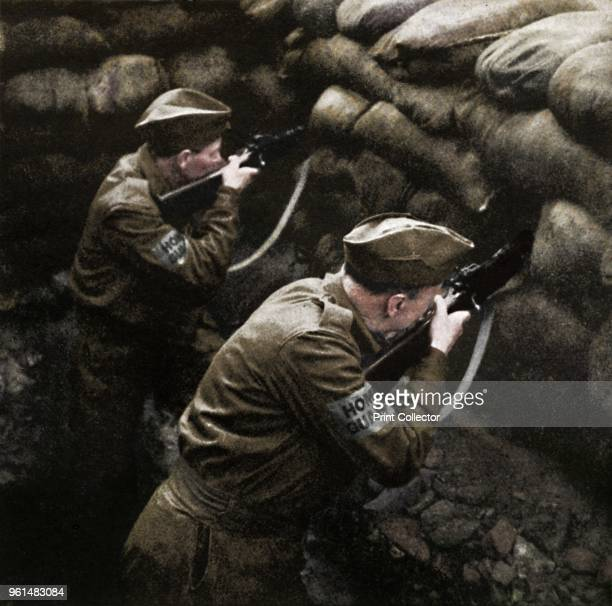 Covering the road block' 1941 Men of the Home Guard in a dugout protected by sandbags aim their rifles ready for action From Air of Glory by Cecil...