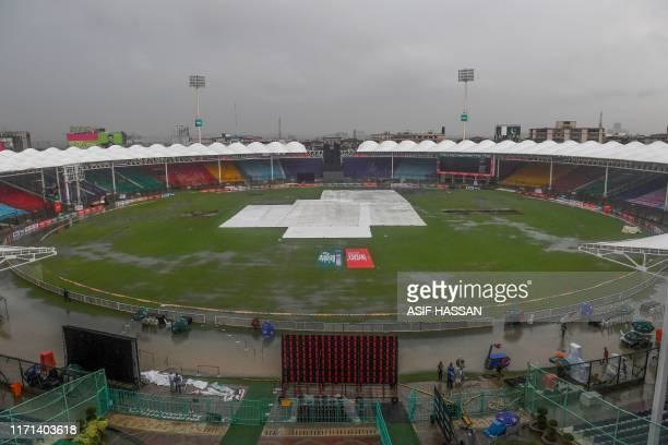 Covers are laid out on the pitch during heavy monsoon rain at the National Cricket Stadium in Karachi on September 27 2019 Incessant rain threatened...
