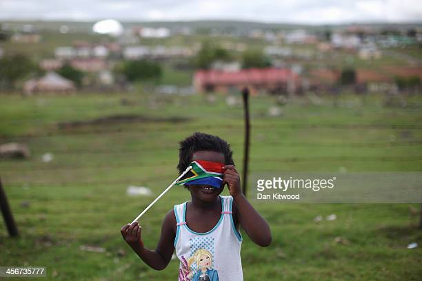 A covers her face with a South African flag near the former South African President Nelson Mandela's home during his state funeral December 15 2013...