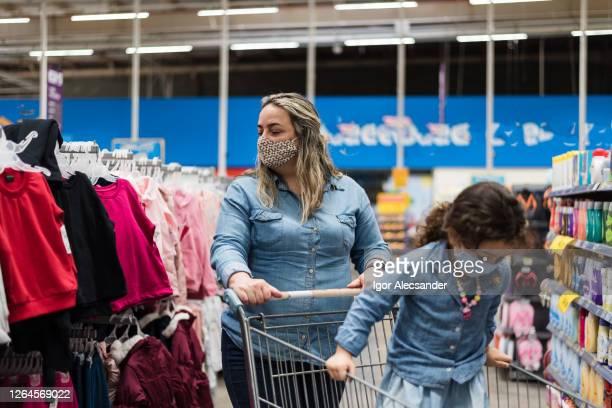 covid 19:スーパーマーケットの衣料品セクションで母と娘 - 中南米 ストックフォトと画像