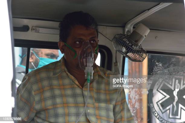 Covid 19 patient wearing an oxygen mask as he waits in an ambulance outside a city hospital before admission. There has been a scarcity of hospital...