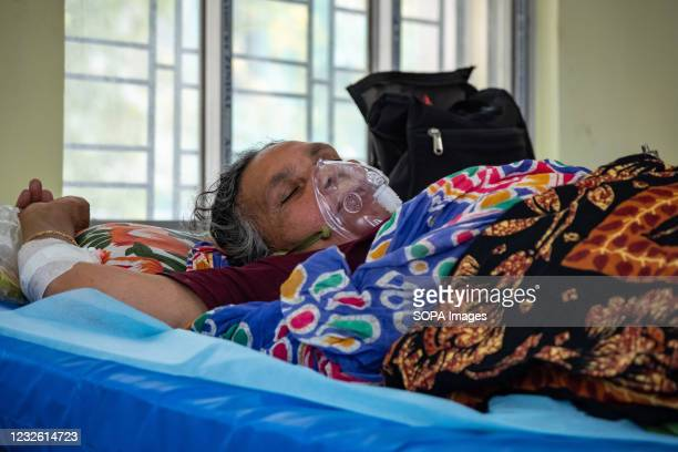 Covid patient wearing an oxygen mask seen lying on a bed inside a newly made Covid ward at Barasat Government Hospital. India's total coronavirus...