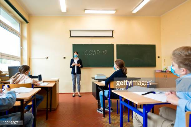 covid-19. a teacher explains epidemic prevention knowledge at a school - teacher stock pictures, royalty-free photos & images